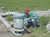 Man kneeling next to irigation pump.