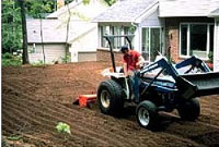 tilling compost into soil during lawn renovation
