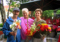 Mark Cain (left) of Dripping Springs Garden presents bouquets to Carol Eichelberger and Jean Mills of Coker, Alabama, at the Fayetteville Farmers' Market.